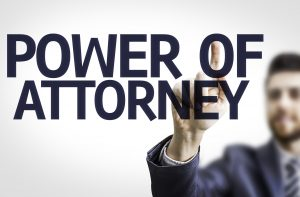 The words power of attorney written on a glass board with a man in the background pointing at the words