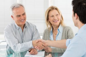 Happy elderly couple shaking the hand of an estate planning attorney